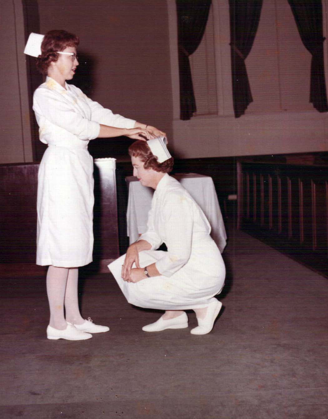 A nurse places nursing cap on head of kneeling Margaret Lanier.